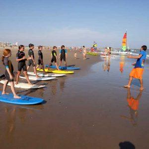 practica sobre la tabla en la playa antes de entrar al agua