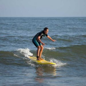 uan de nuestras alumnas de pie en la tabla de surf